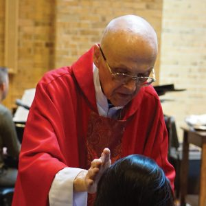 Fr. John anoints a worshiper at a 2017 Anointing Mass