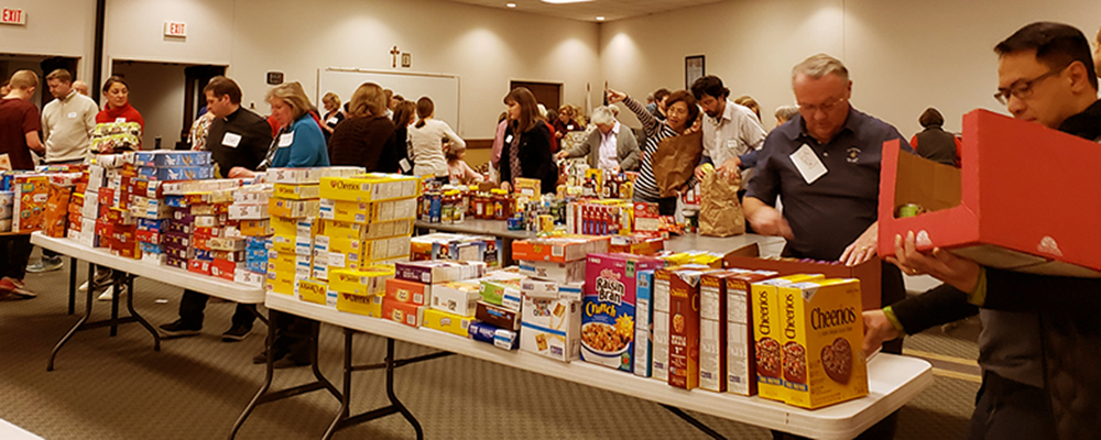 Volunteers fill boxes with food for local families